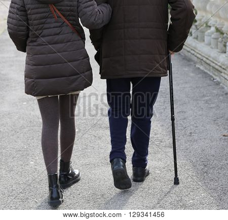 Woman Accompanies The Older Gentleman With Walking Stick