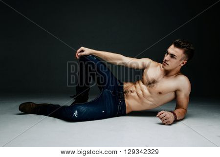 Young fashion topless man lying on the floor isolated on dark background. Strong Athletic Man Fitness Model Torso showing six pack abs