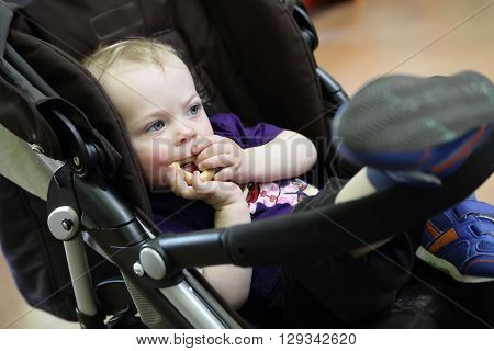 Thinking child eating bagel in a stroller