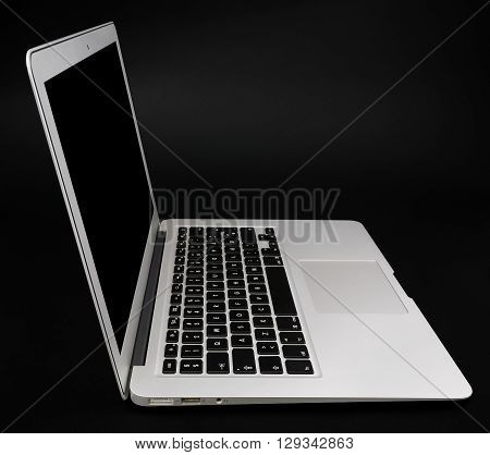White aluminium laptop with black screen on the dark background