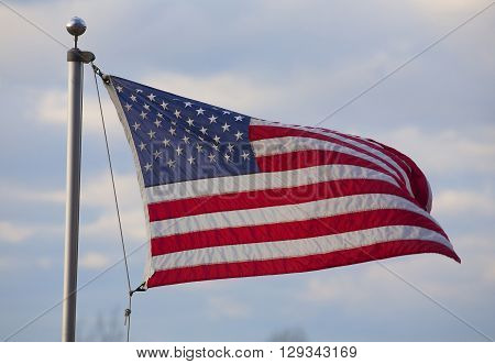 American flag on an aluminum pole with clouds behind