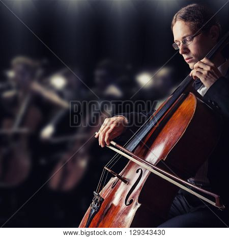 Close-up of cellist playing classical music on cello in the orchestra