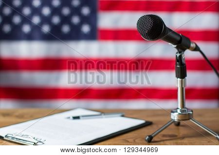 American flag, microphone and paper. Clipboard and microphone beside banner. TV show scenario on table. Notes of news host.