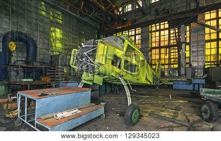 Abandoned aviation factory of small aircraft. The partially-built airplane in a dark industrial building at night