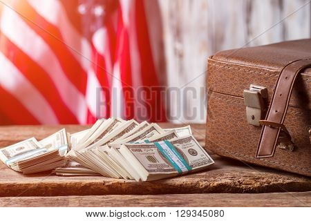US flag, case and dollars. Cash bundles near brown case. There's never enough money. Taxes payed by citizens.