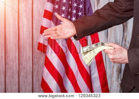 Businessman with dollars giving hand. USA flag, man and money. What a friendly gesture. Partnership is power.