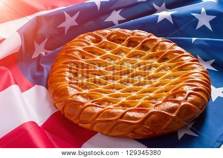 USA flag and a pie. Baked product laying on banner. Greetings from homeland. You're always welcomed.