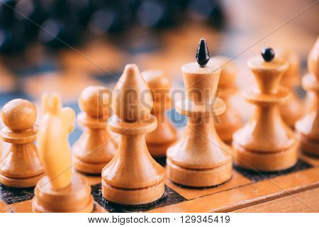 Old Vintage Chess Standing On Wooden Chessboard