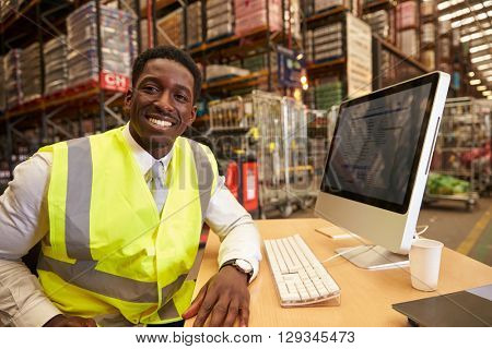 Manager in the on-site office of a warehouse looks to camera