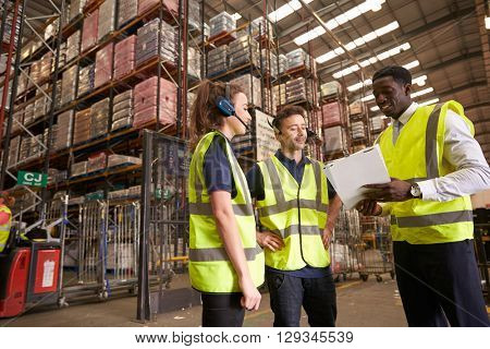 Distribution warehouse manager instructing colleagues