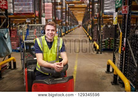 Young man leaning on tow tractor in distribution warehouse