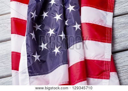 Creased national flag of US. Flag on white wooden background. Banner of three colors. Faith, hope and patriotism.