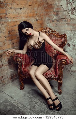 Beautiful sexy long hair woman posing in the camera. Studio shooting in interior. Model sitting in chair. Bright make up red lips black dress. Hot glamorous brunette woman.