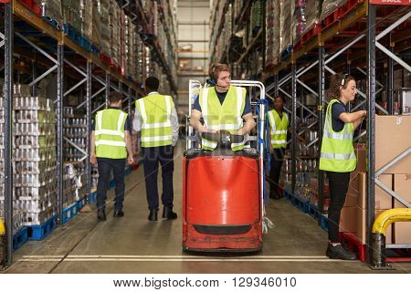 Woman selects box in warehouse for coworker on tow tractor