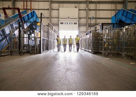 Four colleagues leaving a warehouse approach the exit