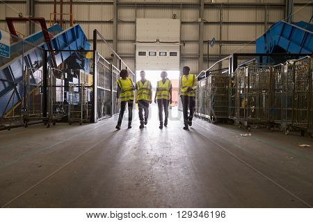 Four colleagues walking into a warehouse, wide view