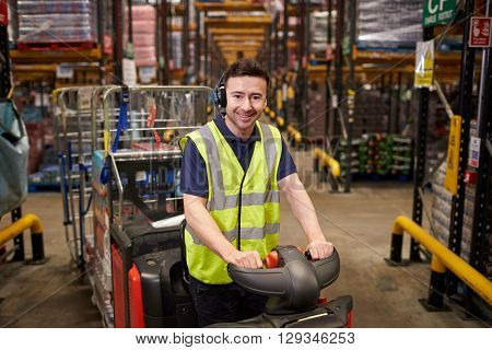 Man on tow tractor at distribution warehouse looks to camera