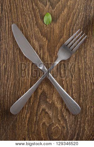 Cutlery on a dark wooden table. Leaf basil.