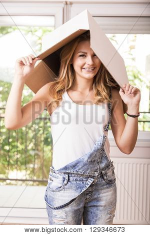 Young girl posing with a cardboard box on her head while unpacking in her new apartment