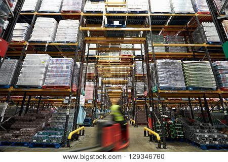 A forklift truck passing though a warehouse, motion blur
