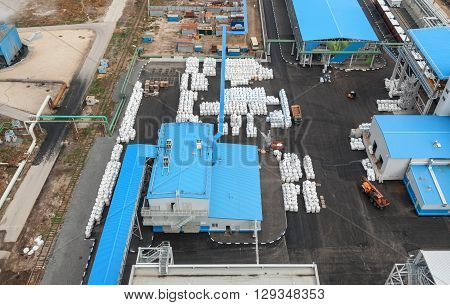 Chemical plant for production of ammonia and nitrogen fertilization on day time. Open area for finished products. Top view. Focus on the center of the frame