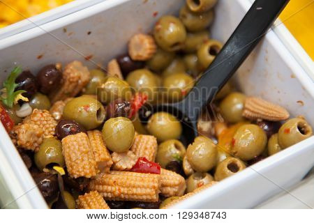 Olives and baby corn in a bowl in a self service salad bar in a hotel canteen