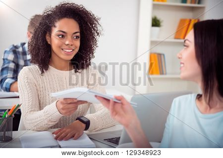 Here you are. Two young cheerful students studying together  helping each other