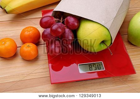 Fresh fruits on red digital kitchen scales over wooden background