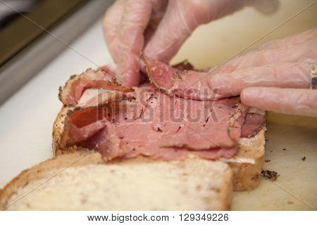 Close up of a person hands preparing ham sandwich in a cafeteria