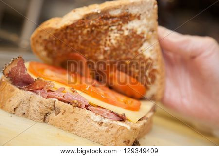 Close up of a person hands showing ham, cheese and tomato sandwich in a cafeteria