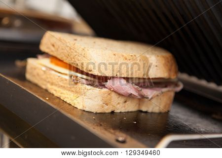 Wholemeal ham, cheese and tomato sandwich in a toaster in a cafe