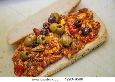 Spicy chicken, olives and baby corn sandwich in a cafeteria