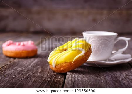 Donut. Sweet food and cup of coffee drink. Rustic wooden table. Bakery sugar doughnut.