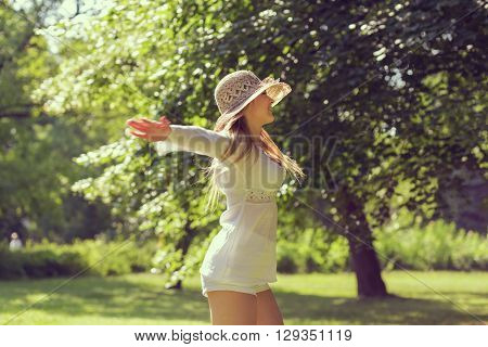 Beautiful blond enjoying in the park on a sunny summer day spinning on the grass with arms widespread