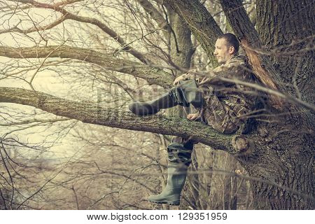Cheerful young man sitting on tree branch looking into the distance and enjoy the scenery. Concept for future, discovery, exploring and dreaming