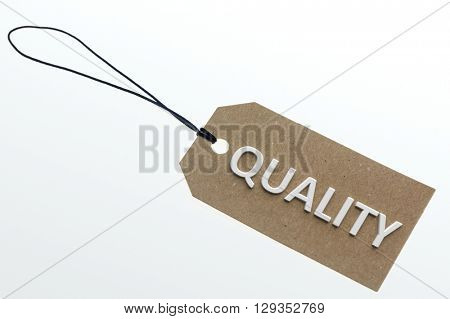 QUALITY word on cardboard tag on white background.Isolated