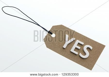 YES word on cardboard tag on white background.Isolated