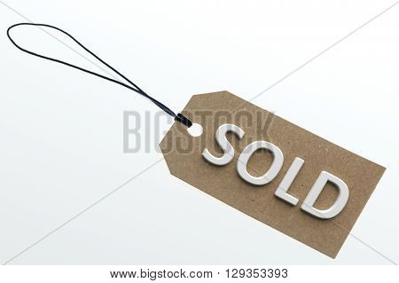 SOLD word on cardboard tag on white background.Isolated