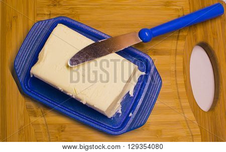 Butter in blue dish and knife on wooden background