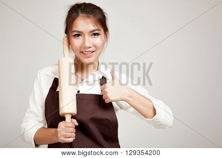 Asian Baker Woman  In Apron Thumbs Up  With Wooden Rolling Pin
