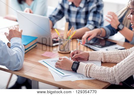 Working place. Concerned people sitting in the circle at the table expressing gladness while being fully involved in work