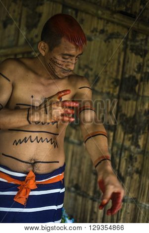 SANTO DOMINGO ECUADOR - JANUARY 26 2015: Indian man Colorados (Los Tsáchila) tribe in national clothes paints hair and body with juice of plants achiote for ritual purposes on January 26 2015 in Santo Domingo Los Rios Ecuador