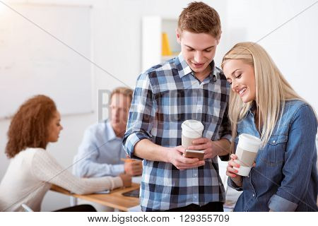 Coffee break. Smiling pleasant young students drinking coffee and laughing while having a break