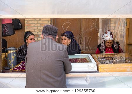 Buckara Uzbekistan - Aprilr 16 2014: Local people and vendors in the market on the side of the Kalon mosque
