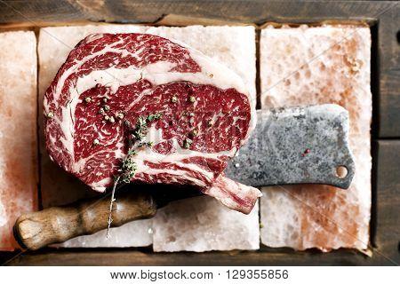 Bone In Rib Eye row Steak on pieces of salt on a wooden board. Stock image. Kitchen knife axe