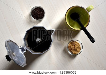Little cup and black spoon with cane sugar, coffee powder and moka