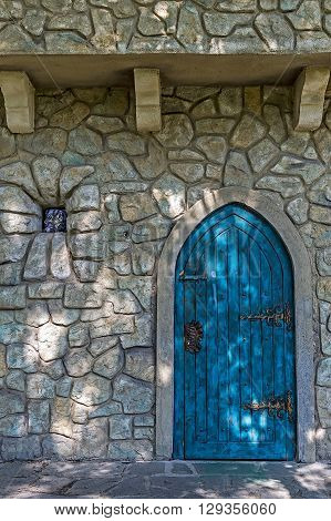 Stone wall texture background with ancient blue door to the castle and small window.