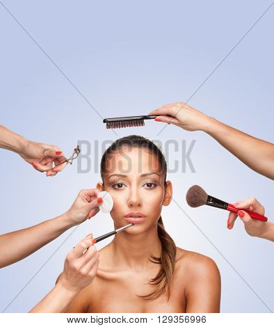 Portrait of young female surrounded by hands with beauty tools looking at camera