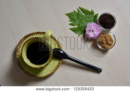 Little cup of dark coffee and black spoon with cane sugar, coffee powder, pink rose and green leaf
