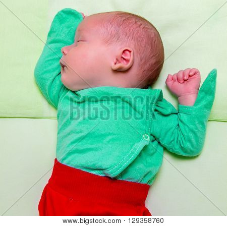 Sleeping newborn in bed, contrast of colors